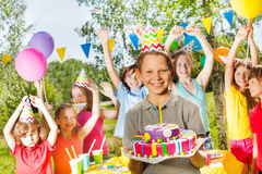 Happy young boy in party hat holding birthday cake Royalty Free Stock Photos