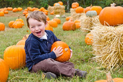 Happy young boy picking a pumpkin