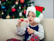 Happy boy playing with a Christmas tree in the background Stock Photography