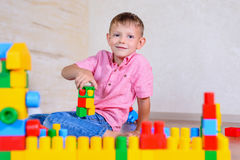 Happy young boy playing with his building blocks Stock Photos
