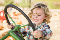 Happy Young Boy Playing on an Old Tractor Outside Royalty Free Stock Photos