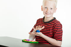 Happy young boy playing with plastic putty Stock Images
