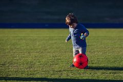 Happy young boy playing with red ball with his mother on green grass Royalty Free Stock Photography
