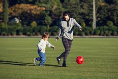 Happy young boy playing with red ball with his mother on green grass stock images