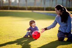 Happy young boy playing with red ball on and his mother green grass stock photo
