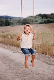 Happy young boy playing on swing in a park Royalty Free Stock Image