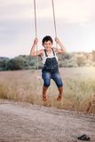 Happy young boy playing on swing in a park Stock Image
