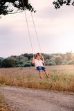 Happy young boy playing on swing in a park. Screaming and having fun Stock Image