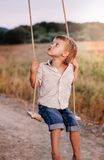 Happy young boy playing on swing in a park. Screaming and having fun Royalty Free Stock Photography