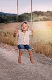 Happy young boy playing on swing in a park Stock Photos