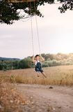 Happy young boy playing on swing in a park Royalty Free Stock Images