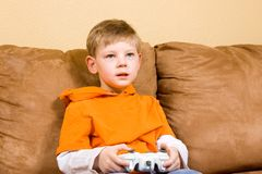 Happy young boy playing video game royalty free stock images