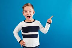 Happy young boy pointing up and holding arm on hip. Happy young boy in sweater pointing up and holding arm on hip while looking at the camera over blue Stock Photos