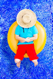 Happy young boy relaxing on a tube in the pool Stock Image