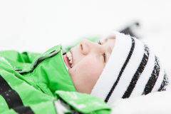 Happy young boy relaxing in the winter snow Royalty Free Stock Photography
