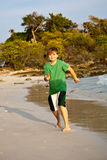 Happy young boy is running along. The beautiful beach Royalty Free Stock Image
