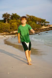 Happy young boy is running along. The beautiful beach Stock Photos