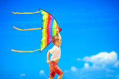 Happy young boy running with kite on sky background Royalty Free Stock Image