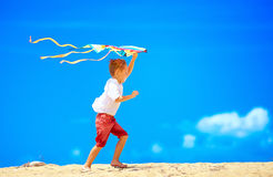 Happy young boy running with kite on sky background Royalty Free Stock Images