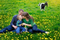 Happy young boy running on meadow with his parents.  Royalty Free Stock Photo
