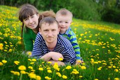 Happy young boy running on meadow with his parents.  Royalty Free Stock Images