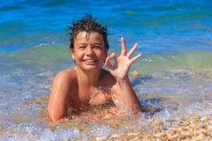 Happy young boy on the sea beach OK Royalty Free Stock Photography