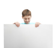 Happy young boy with a sheet of paper. Happy young boy in a cyan t-shirt with a empty copyspace sheet of paper in front of him, composition isolated over the Royalty Free Stock Images