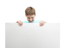 Happy young boy with a sheet of paper. Happy young boy in a cyan t-shirt with a empty copyspace sheet of paper in front of him, composition isolated over the Stock Images