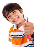 Happy young boy showing the toothbrush. On isoalted background Stock Images
