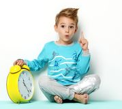 Happy young boy sitting in blue sweater thinking and looking up. With big yellow clock pointing finger up on white background Stock Images