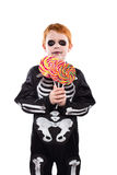 Happy young boy with skeleton costume holding colorful candies Stock Photo