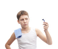 Happy young boy in a sleeveless shirt. Happy young boy in a sleeveless white shirt with a towel over his shoulder and and a shaving razor blade in his hand Royalty Free Stock Image
