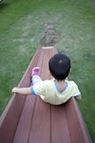 Happy young boy sliding down slide Royalty Free Stock Image