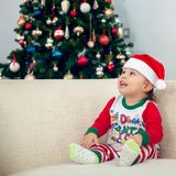 Happy boy playing with Christmas decorations. Happy young boy smiling, playing and having fun with Christmas decorations and a Christmas tree in the background Royalty Free Stock Image