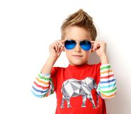 Happy young boy standing in light red shirt looking at the corner in sunglasses. Happy young boy standing in fashion red shirt looking at the corner in Royalty Free Stock Photography