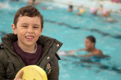 Happy young boy standing by the pool. A happy young boy wearing jacket smiling while standing by a swimming pool Stock Photography
