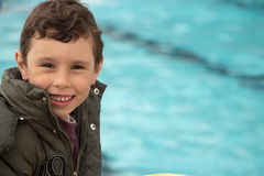 Happy young boy standing by the pool. A happy young boy wearing jacket smiling while standing by a swimming poo Stock Images