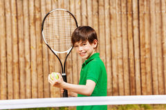 Happy young boy starting tennis set Royalty Free Stock Photography