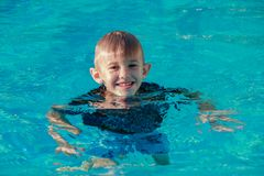 Happy young boy swimming in a pool outdoor royalty free stock photos