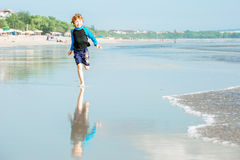 Happy young boy in swimming shorts and blue Stock Photo