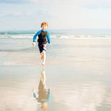 Happy young boy in swimming shorts and rushwest Stock Photos