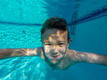 Happy young boy swimming under outdoor pool water in sunny day in South Florida royalty free stock images