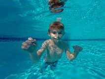 Happy young boy swimming under outdoor pool water in sunny day in South Florida stock photography