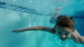 Happy young boy swimming under outdoor pool