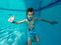 Happy young boy swimming under outdoor pool water in sunny day in South Florida stock image