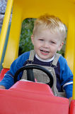 Happy young boy in toy car Stock Image