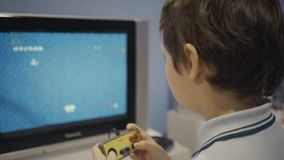 Happy young boy using a retro controller to play a video game. Happy young boy using a retro controller to play a video game stock footage