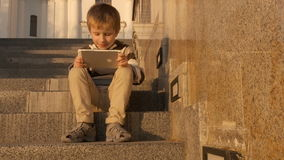 Happy young boy using tablet computer in the park stock video