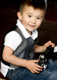 Happy Young Boy in Vest Plays Around With Vintage Camera Royalty Free Stock Image