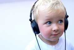 Happy young boy wearing headphones. Listening to music Royalty Free Stock Photos